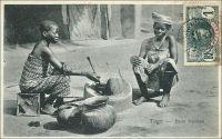 Togo - Beim Kochen (pendant la cuisson). – Cette carte postale, représentant une scène de cuisine dans le sud du Togo au tout début du XXe siècle, est intéressante à plusieurs titres. Elle témoigne en effet de ruptures et de continuités historiques et sociales. Ainsi, elle est issue d'une édition allemande, comme en témoigne la légende, et a donc été prise et publiée avant la première guerre mondiale. Pourtant, elle a été affranchie par un timbre français, donc expédiée après la prise de cette colonie allemande par les forces britannique et française en 1914, événement inaugural de la perte par l'Allemagne de tout son empire colonial. La scène elle-même raconte une vie encore organisée autour de productions locales. Les récipients de terre et de chaudronnerie traditionnelle, les ustensiles de bois et les bijoux sont de fabrications artisanales. Les textiles et la caisse servant de siège à la jeune cuisinière sont déjà des objets importés d'Europe. Aujourd'hui, ils seraient pour la plupart remplacés par des productions industrielles asiatiques. Même certains ingrédients seraient des produits d'importation, comme le bouillon en cube et le concentré de tomate, voire la viande surgelée. Seuls le lieu privilégié pour préparer le repas, la cour de la maison, et la cheville ouvrière de cette opération, une enfant vraisemblablement employée comme domestique, resteraient intangibles.