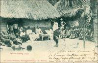 Palaver-Sitzung(Togo). Séance de palabre au Togo. - Ce tableau édifiant célèbre les sages traditions togolaises en matière de négociation. Il semble opportunément scénarisé pour illustrer certaines des options de la politique coloniale allemande. D'une part, il ne peut s'agir d'une scène de vie saisie à l'improviste par le photographe. Le matériel et les temps de pose requis pour capturer une telle image, en ce tout début du XXème siècle, nécessitaient en effet une certaine organisation. Il a sûrement fallu la préparer, la jouer, la rejouer  et attendre suffisamment longtemps –dans une grande immobilité !- pour impressionner la plaque de verre… D'autre part, cette photo porte les indices du message qu'elle est censée véhiculer, en l'occurrence justifier la délégation de l'exercice du droit aux chefs coutumiers. Ainsi, l'image présente clairement l'assemblée telle un tribunal. Elle est présidée par des édiles locaux siégeant en costume presque officiel. L'œil de la population est représenté par l'abondante assistance répartie de part et d'autre de la cour –et de la cours. Enfin le sérieux de la chose et l'adoubement de la colonie sont attestés en la personne d'un officiel allemand en uniforme, consignant les décisions par écrit. Les Allemands avaient en effet pris le parti de confier aux autorités indigènes les tâches de justice. Cette délégation présente plusieurs avantages. Elle fait porter sur les élites locales l'éventuel mécontentement lié à l'application de lois allemandes particulièrement sévères pour les indigènes. Elle permet aussi d'économiser substantiellement sur le personnel colonial dédié. L'économie des dépenses est un principe central dans la gestion du Togo. Ce territoire est considéré comme la colonie modèle par Berlin, car très tôt il rapporte à l'Allemagne plus qu'il ne coûte.
