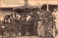 Adjiki, Roi nègre dans son carrosse au milieu de ses Ministres. – Le roi Adjiki, monte sur le trône de Porto Novo en février 1908. Il connait à cette occasion une célébrité inédite dans la presse à sensation française. Cet engouement tient peut être au fait qu'il est le fils et le successeur du roi Toffa - l'allié de la France contre le roi Béhanzin d'Abomey à la fin du XIXème siècle – ou à la nostalgie hexagonale pour les choses de la royauté. Ou encore au passage au Dahomey du grand photographe dakarois Edmond Fortier, accompagnant la visite officielle du ministre des colonies en Afrique de l'Ouest de 1908, depuis son escale sénégalaise. C'est d'ailleurs lui l'auteur de ce cliché joliment composé. Le  Couronnement d'Adjiki est rapporté par Le Petit Journal Illustré, dans son édition du 5 avril 1908 : « Le prince Adjiki, fils de Toffa, coiffé du bicorne à plumes blanches, insigne de la souveraineté, assiste aux fêtes de son couronnement. Nous donnons plus loin, dans notre « variété », de curieux et pittoresques détails sur la façon dont on célébrait jadis, et dont on célèbre aujourd'hui, l'avènement d'un nouveau souverain dans ces contrées de la côte des Esclaves qui sont à présent colonies françaises. C'est le récent décès de Toffa, roi de Porto-Novo, et le couronnement de son fils, le prince Adjiki, qui nous ont fourni l'occasion de donner à nos lecteurs, d'après des documents d'une absolue exactitude, cette intéressante gravure sur les fêtes qui se sont déroulées à Porto-Novo. Adjiki a reçu le bicorne à plumes blanches, insigne du pouvoir, des mains de M. Marchal, lieutenant gouverneur de la colonie française du Dahomey, en même temps qu'un arrêté le nommait « chef supérieur des territoires français du Bénin ». De ce fait, Adjiki a pour attribution le concours à l'exécution de toutes les mesures prescrites par le lieutenant gouverneur ou par le président de Porto-Novo. Il intervient notamment lorsqu'il en est requis, auprès des chefs de région, de village ou de 