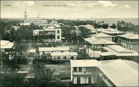 Lomé, Stadtteil der Europäer. - Cette photo du « quartier des Européens » de Lomé à l'époque allemande ne représente pas, paradoxalement, le quartier appelé  Yovokomé, « le village des blancs » en mina, l'une des langues vernaculaires. En réalité, elle montre la zone commerçante de la ville - avec la cathédrale achevée en 1902 au fond - où exerçaient et logeaient marchands européens et africains. Le quartier administratif, abritant les services de la colonie et les logements des fonctionnaires allemands, justement désigné comme Yovokomé par les Loméens, se trouve dans le dos du photographe. La structure de la ville, avec ce quartier administratif un peu à l'écart du centre historique, tient à sa vocation commerciale initiale. Là, et contrairement aux autres capitales du continent où l'administration a accaparé tous les sols urbains, la propriété privée et individuelle des terrains est reconnue dès les origines. Les autorités font d'ailleurs dresser un cadastre dès leur arrivée en 1896, bien après l'installation des commerçants il est vrai. Ceux-ci, venus faire fortune, achètent et revendent les lots immobiliers comme toute autre marchandise, au point qu'il y a eu plus de mutations foncières dans la ville au cours de la brève période allemande (1884-1914) que depuis ! Les autorités coloniales se sont installées en bordure ouest du centre si convoité, créant une zone administrative géographiquement distincte du pôle des affaires. Cette séparation en fonction des activités, matérialisée au sol par le tracé ferroviaire, existe toujours aujourd'hui.
