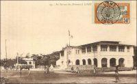 Le Bureau des Douanes à Lomé. – Ce bâtiment, construit en 1903 par les Allemands juste en face du wharf, a été démoli en 1983, laissant place à un centre commercial moderne comptant des salles de cinéma, un casino, une boite de nuit et un hôtel. Les douanes jouaient un rôle capital dans le dispositif colonial allemand. Elles fournissaient en effet la majeure partie des ressources budgétaires du Togo, qui finit par ne plus rien coûter à la métropole à partir de 1906. Les Allemands considéraient de ce fait le Togo comme « Musterkolonie », la colonie modèle. Les marchandises pour tout le territoire, qui devaient être obligatoirement débarquées par le wharf -et donc directement devant la douane-, étaient soumises à une taxe de 10%. Seuls certains articles, comme les sacs, les bouteilles ou les wagons, bénéficiaient d'une franchise douanière. Les Anglais et les Français qui succèdent aux Allemands après la défaite locale de 1914, maintiennent dans un premier temps un système douanier comparable à celui de leurs prédécesseurs. Ensuite, tandis que les Anglais adoptent le même régime douanier au Togo britannique qu'en Gold Coast, les Français instaurent au Togo sous mandat un statut moins favorable qu'au Dahomey et créent ce faisant une concurrence entre les deux territoires mitoyens qui obligea à rétablir un poste de douane à Aného et un contrôle de la frontière sur le Mono. Progressivement, la situation est normalisée, et peu avant la seconde guerre mondiale le régime douanier des deux territoires est aligné sur celui du reste de l'AOF.