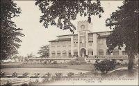Lomé, le Palais du Gouverneur. - Construit de 1898 à 1905, il abritait au rez-de-chaussée les bureaux et à l'étage les appartements du gouverneur, selon le modèle habituel des bâtiments coloniaux. Le gouverneur August Kohler (1858 – 1902), qui était au Togo depuis 1895, décida en 1898 l'emplacement à 250 m de la plage. Pour que l'ensemble de l'édifice puisse être vu depuis les navires en mer, et ce malgré un talus qui bordait le rivage, il reçu un sous-bassement de 3,50 m. Sur ce cliché, on distingue, au mat de drapeau du bâtiment, les couleurs françaises. L'édifice devait continuer en effet à abriter l'exécutif du Togo, durant l'occupation britannique, entre 1914 et 1920, puis sous le mandat français et même après l'indépendance, jusqu'à la construction de la nouvelle présidence, sur un terrain mitoyen, en 1970. Le journaliste Jean Martet raconte ainsi sa visite au Palais en 1933, à l'époque le gouverneur qui représente Paris dans ce territoire confié à la France par la SDN est Robert de Guise (dans cette fonction entre 1931 et 1933) : « Le bureau de M. de Guise est au rez-de-chaussée de cette grande construction vaguement moyenâgeuse qui a été bâtie par les Allemands face à la mer et qu'on appelle, pompeusement, le Palais du Gouvernement. Les appartements du gouverneur sont au premier : de grandes pièces, claires et fraiches, avec vue sur cette mer sans une voile, sans une fumée, et les mendiants du parc, les palmiers de la belle et large route qui borde la plage. Nous trouvâmes Mme de Guise comme elle était en train de donner des ordres à son chauffeur, lequel est prénommé Momo. Momo est un noir vêtu de blanc, avec, à la main, une belle casquette, Mme de Guise est une femme souriante et charmante. Elle vint à moi et me dit : - Il y a par ici une ville qui s'appelle Palimé. Palimé a élu l'année dernière sa plus belle négresse, Miss Palimé. Momo est passé par là et a enlevé Miss Palimé. J'aime beaucoup Momo. Je m'assis. C'était un grand salon avec de jolis meubles 