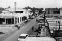 Lomé, rue de l'église (dans les années 1960). – La capitale togolaise connait un fort développement à partir de la fin de la seconde Guerre mondiale. L'envolée du cours des produits tropicaux, les forts investissements publics et l'afflux de populations rurales, qui ont fuit les rigueurs de l'effort de guerre dans les campagnes, contribuent à l'explosion démographique et spatiale de la ville. Sa population bondit ainsi de 18 000 à 33 000 habitants entre 1938 et 1950, pour atteindre 85 000 habitants en 1958. Quittant la seule bande côtière, les quartiers s'étendent progressivement sur les vastes cocoteraies environnantes.  Vers le nord-ouest, sur les terres de la famille Olympio, un lotissement chic voit le jour et, plus loin, le quartier de Nyékonakpoé sort de terre. Vers le nord-est, Bé, son marché et sa gare – une zone jusqu'ici non prise en compte dans les dénombrements de la population loméenne – sont rejoints par les faubourgs. Vers le nord, la lagune est atteinte, puis franchie. Le plateau de Tokoin est progressivement investi, d'abord par les plus pauvres, puis par de grandes infrastructures publiques comme l'hôpital (l'actuel CHU sur le site de l'ancien terrain d'aviation) en 1954, le camp militaire, le collège Saint-Joseph entre 1948 et 1950… Parallèlement, la ville se modernise. Les biques d'argile, matière première justement prélevée sur le plateau de Tokoin et cuite avec les combustibles tirés des cocoteraies, cèdent le pas au parpaing de ciment dans la construction. L'électrification gagne du terrain, au-delà du quartier du wharf où elle avait débuté en 1926, et les rues sont goudronnées jusqu'au Boulevard Circulaire, notamment grâce aux crédits FIDES (Fonds d'investissement pour le développement économique et social d'outre-mer) crée en 1946.