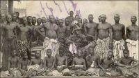 Adjiki, roi de Porto-Novo, ses ministres et sa cour. – Le roi Adjiki, monté sur le trône de Porto Novo en février 1908, connut une célébrité inédite dans la presse à sensation française. Peut être parce qu'il était le fils et le successeur du roi Toffa - l'allié de la France contre le roi Béhanzin d'Abomey à la fin du XIXème siècle – ou par nostalgie des choses de la royauté, son couronnement fut rapporté par Le Petit Journal Illustré, dans son édition du 5 avril 1908 : « Le prince Adjiki, fils de Toffa, coiffé du bicorne à plumes blanches, insigne de la souveraineté, assiste aux fêtes de son couronnement. Nous donnons plus loin, dans notre « variété », de curieux et pittoresques détails sur la façon dont on célébrait jadis, et dont on célèbre aujourd'hui, l'avènement d'un nouveau souverain dans ces contrées de la côte des Esclaves qui sont à présent colonies françaises.  C'est le récent décès de Toffa, roi de Porto-Novo, et le couronnement de son fils, le prince Adjiki, qui nous ont fourni l'occasion de donner à nos lecteurs, d'après des documents d'une absolue exactitude, cette intéressante gravure sur les fêtes qui se sont déroulées à Porto-Novo.  Adjiki a reçu le bicorne à plumes blanches, insigne du pouvoir, des mains de M. Marchal, lieutenant gouverneur de la colonie française du Dahomey, en même temps qu'un arrêté le nommait « chef supérieur des territoires français du Bénin ». De ce fait, Adjiki a pour attribution le concours à l'exécution de toutes les mesures prescrites par le lieutenant gouverneur ou par le président de Porto-Novo. Il intervient notamment lorsqu'il en est requis, auprès des chefs de région, de village ou de quartier pour les maintenir dans l'obéissance totale en toutes circonstances ou pour y maintenir les habitants du cercle de Porto-Novo. Il remplit les fonctions judiciaires qui peuvent ou pourront lui être dévolues par les actes régissant la matière.  Le prince Adjiki reçoit, en cette qualité de chef supérieur un traitement annuel de 2