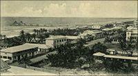 Lomé, Hamburger Strasse (vers 1905). – Connue à l'époque allemande sous le nom de Hamburgerstrasse, la rue du commerce est le centre d'affaire historique de la capitale togolaise. La ville s'est d'ailleurs constituée autour de sa vocation commerciale, à partir des années 1870 : des marchands Ewé, installés sur la côte pour mener la traite légitime (l'huile de palme essentiellement) avec les navires européens, sont venus se fixer en bordure de la frontière est de la Gold Coast, pour échapper aux lourdes taxes douanières britanniques. Aux pionniers se sont bientôt joints des commerçants Mina venus de l'est et Haoussa descendus du nord. Au début des années 1880, des compagnies européennes, allemandes notamment, s'installent à Lomé, alors appelée Bey Beach. C'est sur l'initiative des commerçants allemands de Lomé – qui se sentaient légitimement menacés par les autorités coloniales anglaises, elles-mêmes exaspérées par cette concurrence à leurs portes - que l'explorateur Nachtigal s'arrête là, signe un traité et proclame le protectorat de l'empire allemand sur le Togo en 1884. – Vraisemblablement prise depuis la galerie à l'étage de la mission catholique, cette photo montre la rue d'est vers l'ouest, c'est-à-dire schématiquement depuis la cathédrale vers le bâtiment de la douane allemande (démolie en 1983, pour laisser place à un centre commercial moderne comptant des salles de cinéma, un casino, une boite de nuit et un hôtel). On distingue au premier plan le toit de l'école catholique et à droite le terrain de boule, entouré de murs et où sera construit par la suite le bâtiment de l'UAC (United Africa Company). L'état du wharf, qui est achevé et ne compte que deux grues, situe la photo vers 1905 ; il sera par la suite rallongé de 50 m et doté de nombreux autres dispositifs de levage.