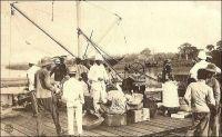 Appontement de Porto-Novo. Avez-vous quelque chose à déclarer ? – Il s'agit vraisemblablement du débarcadère gouvernemental de Porto-Novo, situé sur la lagune à l'ouest des installations portuaires commerciales et relié au Palais du gouverneur par l'avenue William Ponty. Ce type d'ouvrage était courant dans la ville, car la lagune constitua longtemps l'unique voie de communication. Aussi, l'activité commerciale se développa autour de ce cordon qui mène vers Cotonou, où étaient organisées les rades foraines permettant de charger et décharger les navires et où fut ensuite édifié un wharf. Les maisons de commerce européennes, arrivées dans la ville avant et après le traité de protectorat français de 1863, installèrent chacune leur propre appontement sur la lagune, pour assurer le trafic des marchandises importées et exportées. Parfois même, des petits canaux, appelés body et accessibles aux embarcations, furent creusés pour s'approcher de la lagune. Les abords de la lagune étant trop marécageux pour bâtir des installations solides, les  négociants s'implantèrent autour du marché traditionnel, en ménageant des chemins de portage et roulage sur talus pour rallier leurs appontements. – Le commentaire humoristique de cette carte postale, « avez-vous quelque chose à déclarer ? », fait malicieusement allusion aux droits de douanes, qui furent un enjeu décisif dans les politiques coloniales de cette région très disputée par les commerçants européens et africains.