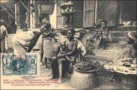 Porto-Novo, marchandes de colas et autres denrées indigènes. - « Le voyageur qui visite pour la première fois Porto-Novo est intéressé par le spectacle des rues. Celles-ci sont en effet très animées : on ne rencontre que femmes portant des caisses de genièvre, de muscat, manœuvres roulant des tonneaux de tafia, indigènes se rendant aux factoreries avec leurs pots d'huile de palme ou avec leur sac d'amande.Les marchandes à la criée ne sont pas inconnues. Chacun peut acheter, dans la rue, la nourriture habituelle de l'indigène : poisson fumé et bouteille d'acaça (farine de maïs bouillie). Dans les cuisines établies en plein vent, on vend au passant des friandises qui sortent toutes chaudes de l'huile de palme bouillante… » (1). Cette carte postale fait partie du travail du photographe et éditeur dakarois Edmond Fortier (1862-1928). Elle appartient à un reportage qu'il mena dans le sud du Dahomey en 1908, alors qu'il accompagnait, depuis l'escale de Dakar, le voyage officiel accompli sur la côte oust africaine par le Ministre des colonies Raphaël Milliès-Lacroix. Sources : (1)Hagen, A, « La colonie de Porto-Novo et le roi Toffa » dans, Revue d'ethnographie [ dir. Hamy, Ernest], Paris, éd. Ernest Leroux, 1887.