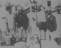 Fonctionnaires indigènes de la poste impériale allemande à Lomé. – Le courrier, avant la mise en service du chemin de fer au Togo en 1905, était acheminé à pieds. Les employés des postes partaient de chaque extrémité de la route – d'Aného vers Lomé et de Lomé vers Aného pour la voie côtière - et se rencontraient à mi-chemin en un point convenu où ils échangeaient leur chargement postal avant de rebrousser chemin en direction de leur bureau de poste d'origine. Entre Lomé et Aného, l'échange avait lieu au niveau du poteau télégraphique n°221, et l'ensemble du trajet prenait la journée, de 7 heures à 16 heures. Entre Kpalimé et Lomé – un service entre les deux villes fut créé en 1902 - il fallait compter trois jours. La mise en service du train permis de raccourcir considérablement les délais, notamment sur les longues distances vers l'intérieur du pays. En 1912, le service postal allemand au Togo était constitué de 16 bureaux de poste disposant d'un télégraphe, de 6 bureaux auxiliaires, et d'un réseau de téléphone urbain. Cette même année, 486 606 lettres furent acheminées dans la colonie, ainsi que 15 116 paquets, 39 695 télégrammes, 113 296 exemplaires de journaux ; 54 285 communications téléphoniques furent passées.