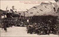 Porto-Novo, Indigènes dans la Cour du roi Toffa. – Dix-neuvième souverain de la dynastie des princes Allada à exercer le pouvoir sur le royaume de Porto-Novo, Toffa eut également le plus long règne : monté sur le trône en 1874, il y demeura jusqu'à sa mort en 1908. Signataire d'un traité d'amitié et de protectorat avec la France en 1883, il laisse une image controversée dans l'histoire dahoméenne : c'est pour le protéger des attaques du royaume d'Abomey – et pour défendre leurs intérêts territoriaux et commerciaux - que les Français ménèrent la campagne militaire de 1892, aboutissant à la destitution et au bannissement du jeune roi Béhanzin d'Abomey.