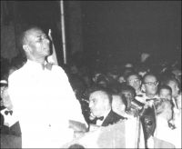 Au soir du 26 avril 1960, Sylvanus Olympio et les Togolais attendent les 101 coups de canon qui marqueront, à minuit, l'indépendance formelle du Togo. – Proclamée dès les premiers instants du 27 avril,  l'indépendance était plus une cérémonie solennelle qu'un bouleversement institutionnel. Elle intervenait en effet deux ans jour pour jour après l'arrivée de S. Olympio à la tête du premier gouvernement du Togo indépendant, le 27 avril 1958. Des accords signés entre la République autonome du Togo (proclamée le 30 août 1956) et la France, venaient alors de donner quasiment tous les pouvoirs – hormis les relations extérieures, la monnaie, les changes et la Défense, conservés par la tutelle française - au chef de la majorité à l'assemblé territoriale togolaise. Ces dispositions avaient été négociées par Nicolas Grunitzky, adversaire politique et propre beau-frère d'Olympio, aux affaires depuis 1951, auprès de l'ONU et de Paris - ancienne colonie allemande, le Togo était sous la tutelle des Nations Unies, confié par celles-ci à la gestion de la France.  Ce statut que n'auraient pas renié les plus nationalistes devait finalement faire de  Sylvanus Olympio l'homme des indépendances – technique d'abord, formelle ensuite -, le parti de Grunintzky, homme lige de Paris aillant perdu les élections législatives de 1958. Les festivités du 27 avril 1960, furent, de l'avis de tous mémorables et parfaitement orchestrées. La radiodiffusion d'Outre-Mer rendit compte de l'événement, l'INA en propose un intéressant extrait en archive : http://www.ina.fr/histoire-et-conflits/decolonisation/audio/PHD86080309/ceremonie-d-independance-du-togo-a-la-chambre-des-deputes-togolaise.fr.html