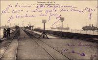 Wharf et rade de Cotonou. – Appelé à soutenir la vocation portuaire de la ville et à faciliter le débarquement des troupes alors que la guerre se profile – en 1892 -, le wharf de Cotonou est construit entre 1891 et 1893. Long de 300 mètres, il ouvre au trafic commercial le7 mai 1893. Au départ, il ne permet aux navires d'accoster qu'au rythme d'un par mois. Insuffisant pour absorber tout le trafic de fret et de passagers du Dahomey - hormis celui avec Lagos qui passe par voie fluviale sur la lagune et le cabotage local résiduel au port de Grand Popo sur l'embouchure du Mono -, il est remplacé en 1928 par un édifice plus important (400 mètres) et mieux équipé. Les navires sont chargés et déchargés directement au mouillage en rade foraine, à un kilomètre du wharf, grâce à une flottille de 26 baleinières de 15 à 25 tonnes et de 8 remorqueurs de 60 à 75 chevaux. Treize grues électriques, d'une capacité de levage allant de 10 à 20 tonnes, permettent de transborder les charges des baleinières sur le wharf où le transport est relayé par voie ferrée. Aussi utile qu'il soit, ce dispositif montre bientôt ses limites. Les moyens relativement modestes et les manipulations complexes qu'ils supposent occasionnent des pertes importantes dans les cargaisons : les coûts sont trois fois plus élevés qu'au port de Dakar. De plus, ces équipements ne permettent guère de traiter plus de 1000 tonnes par jour et, compte tenu des avaries, la capacité annuelle plafonne à 300 000 tonnes. Enfin en période de pointe, les délais se prolongent, provoquant un inconfort certain pour les passagers qui attendent d'être débarqués par le fameux panier. En 1964, la capitale du Dahomey se dote d'un port en eau profonde, remplaçant définitivement le wharf et le système de rade foraine devenus obsolètes. – Cette carte, éditée sous la signature « Collection Géo Wolber, Dahomey », est une curiosité. Elle fait partie des séries produites et diffusées après la première guerre mondiale – et jusqu'en 1937 - par l