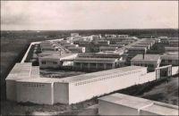 Lomé, vue générale de l'hôpital de Tokoin - Le CHU de Lomé, bâti par tranches entre 1951 et 1954 sur l'emplacement de l'ancien aérodrome de 1931, remplace l'hôpital Reine-Charlotte de Lomé, principale institution hospitalière du Togo depuis son ouverture en 1909. Son implantation sur le plateau de Tokoin initie l'extension de la ville au-delà de la lagune. On voit sur cette photo, qui doit immédiatement suivre les travaux – il n'y a encore aucun arbre dans l'enceinte de l'hôpital –, que le quartier est totalement vide. Tokoin va dès lors rapidement se peupler et s'étendre, comptant 7000 habitants en 1959, et rassemblant de nos jours plus des deux tiers de la population de Lomé. L'architecte de ce nouvel établissement hospitalier, Henri Crouzat, est également à l'origine du plan d'urbanisme de Lomé datant de 1948. Il reste cependant plus connu pour son oeuvre littéraire. « Azizah de Niamkoko », publié en 1959 et porté à l'écran en 1986 par Patrick Jamain sous le titre de « Azizah, fille du fleuve », est un célèbre roman à clef décrivant le Togo colonial. Il aurait valu à son auteur d'être réexpédié manu militari en métropole. « L'île du bout du monde », son premier roman avait été édité en 1958 et porté à l'écran la même année par le réalisateur français Edmond T. Gréville ; Crouzat assurant à la fois l'adaptation et les dialogues.
