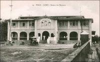 Lomé, Bureau des Douanes. – Ce bâtiment, construit en 1903 par les Allemands juste en face du wharf, a été démoli en 1983, laissant place à un centre commercial moderne comptant des salles de cinéma, un casino, une boite de nuit et un hôtel. Les douanes jouaient un rôle capital dans le dispositif colonial allemand. Elles fournissaient en effet la majeure partie des ressources budgétaires du Togo, qui finit par ne plus rien coûter à la métropole à partir de 1906. Les Allemands considéraient de ce fait le Togo comme « Musterkolonie », la colonie modèle. Les marchandises pour tout le territoire, qui devaient être obligatoirement débarquées par le wharf -et donc directement devant la douane-, étaient soumises à une taxe de 10%. Seuls certains articles, comme les sacs, les bouteilles ou les wagons, bénéficiaient d'une franchise douanière. Les Anglais et les Français qui succèdent aux Allemands après la défaite locale de 1914, maintiennent dans un premier temps un système douanier comparable à celui de leurs prédécesseurs. Ensuite, tandis que les Anglais adoptent le même régime douanier au Togo britannique qu'en Gold Coast, les Français instaurent au Togo sous mandat un statut moins favorable qu'au Dahomey et créent ce faisant une concurrence entre les deux territoires mitoyens qui obligea à rétablir un poste de douane à Aného et un contrôle de la frontière sur le Mono. Progressivement, la situation est normalisée, et peu avant la seconde guerre mondiale le régime douanier des deux territoires est aligné sur celui du reste de l'AOF. - La photo est prise depuis le wharf construit par les Allemands, dont on aperçois une partie de la rambarde à droite de l'image. Cette carte postale a été éditée par Alex Accolatse. Ce notable loméen
