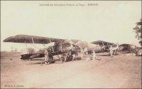 Sokodé, l'arrivée des aéroplanes français au Togo. – L'histoire de l'aviation togolaise est assez ancienne, puisque les autorités coloniales ont fait établir, dès l'entre guerres, une série de terrains de secours, dont 2 (Lomé et Mango) ouverts à l'année et 23 secondaires uniquement praticables en saison sèche. Ces installations sommaires étaient destinées à répondre aux besoins croissants des raids touristiques. A la même époque, en 1934 ou 1936 selon les sources, l'aéroclub de Lomé voit le jour, sous l'impulsion de l'avocat Viale qui l'animera jusqu'en 1939. Les pilotes amateurs volent alors sur un monoplan Potez de type 60 P2 et sur un biplan Caudron C59. L'aéroclub du Golfe, qui est le plus ancien d'Afrique de l'Ouest, fonctionne encore 75 ans plus tard. Le Togo fut également le pionnier dans la région pour la construction aéronotique amateur, avec un monoplace monoplan à aile basse mu par un moteur Volkswagen, conçu et fabrique dans les années 1970 par le mécanicien Jean Camérini. – Carte postale éditée par A. Accolatsé. Alex Accolatse avait commencé sa carrière de photographe à la toute fin du XIXème siècle en Gold Coast, avant de venir s'installer en 1900 à Lomé où il exerça jusqu'en 1956 et s'éteignit en 1975 à 95 ans.