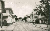 Lomé, la rue du Commerce. – La plus ancienne rue commerciale de Lomé, appelée Hamburgerstrasse du temps de la colonie allemande, regroupait la plupart des factoreries de la place, et le siège local des compagnies maritimes et de négoce. On y trouvait notamment, aux côtés du temple et de la librairie évangélique, la firme Bödecker-&-Meyer,  les bureaux de l'armateur allemand Woerrmann, devenus ministère du commerce dans les années 1970. S'y trouvait aussi l'hôtel  Vogt, qui partageait le marché avec l'hôtel Kaiserhoff. Un peu plus tard, ils cédèrent la place à l'Hôtel du Golfe. Celui-ci est explicitement mentionné en 1941, dans l'enquête menée par les autorités militaires françaises de Lomé pour éclaircir le passage vers la colonie britannique voisine de la Gold Coast, de deux matelots de l'aviso La Gazelle. - Alex Accolatse, à qui l'on doit ce cliché, avait commencé sa carrière de photographe à la toute fin du XIXème siècle en Gold Coast. Il vint s'installer en 1900 à Lomé, où il exerça jusqu'en 1956 et s'éteignit en 1975 à 95 ans.