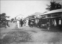 Lomé, la rue du grand-marché, vers 1910. – On aperçoit la maison dite du Dr Anthony qui, bâtie en 1904 par la firme allemande Oloff, fut vendue en 1924 comme « bien ennemi » et acquise par la famille Anthony qui la possède encore. « La ville se divise en plusieurs quartiers. Au bord de la mer se trouvent des comptoirs ; il y en a quatorze à l'heure actuelle. Vers l'ouest habitent des gens qui viennent du territoire anglais, et qui se sont établis ici. Vers le sud-ouest, ce sont les habitations des haoussa, de toutes petites huttes rondes ressemblant à des ruches d'abeilles. […] La ville est organisée sur le modèle européen avec de larges rues. La rue du Marché est, jusqu'à présent, la plus belle, bordée de chaque côté par les comptoirs  des marchands ». Source : Description de Lomé en 1892 par le R. P. Shaeffer, cité par Muller, R. P. K., Histoire de l'église au Togo, Lomé, Bon pasteur, 1968.