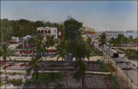 Lomé, le Cercle vu du phare. – Il doit s'agir de l'ancien cercle de Lomé-ville, devenu école de la Marina par la suite. La photo a été prise depuis l'ancien phare, installé en 1933 à côté du wharf français, et qui resta quelques années dans les jardins de l'hôtel Le Bénin après sa construction en un temps record pour être livré à l'occasion de l'indépendance le 27 avril 1960. Le phare fut  ensuite démonté, en 1968, pour prendre place sur château d'eau de Bè où il fonctionne actuellement.