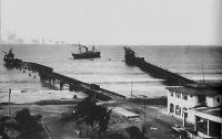 Lomé, la douane et les deux wharfs en 1928. – Le wharf allemand, à gauche sur l'image, fut construit entre 1902 et 1904, assurant l'essor économique de la ville qui était alors la seule dans toute la région à disposer d'une telle installation.  Mais une violente tempête, dans la nuit du 16 au 17 mai 1911, devait emporter la partie centrale de l'édifice, ne laissant que l'extrémité qui avait était ajoutée en 1908. Des travaux de restauration, entrepris en 1912,  aboutirent au contournement de la passerelle brisée, donnant au wharf réparé sa silhouette coudée si caractéristique. Le wharf français, à droite sur l'image, est construit entre 1925 et 1928. Profilé et perpendiculaire à la barre (et non plus à la côte comme le wharf allemand), il est plus résistant et offre une capacité de 700 tonnes par jour (le double du wharf allemand).